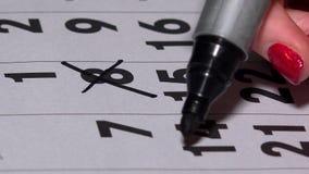 Hand mit der schwarzen Markierung, die gelegentliche Tage auf Kalender kreuzt stock footage