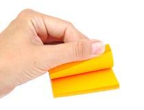 Hand mit einem Block von gelben Post-Itanmerkungen oder Stockbild