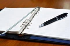 Hand mit einem Federschreiben auf Weißbuch Stockbild