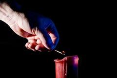 Hand mit einem Match beleuchtet eine rote Kerze Lizenzfreie Stockfotografie