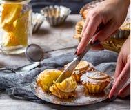 Hand mit einem Messer schneidet den Zitronenkleinen kuchen Lizenzfreie Stockfotos
