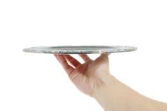 Hand mit einem silbernen Tellersegment Stockbild