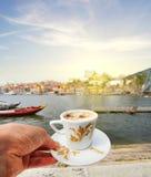 Hand mit einem Tasse Kaffee und einer Ansicht von Duero-Flussufer von der Dom Luiz-Brücke, Porto, Portugal Lizenzfreies Stockfoto