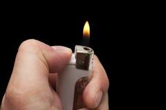 Hand mit einem Zigarettenfeuerzeug Lizenzfreie Stockbilder