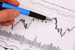 Hand mit einer Feder, die auf Finanzdiagramm zeigt Stockbilder