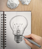 Hand mit einer Glühlampe der Federzeichnung auf Anmerkungsbuch Lizenzfreie Stockfotografie