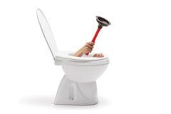 Hand mit einer Gummisaugschale, die von der Toilettenschüssel herauskommt Stockbild