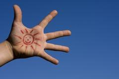 Hand mit einer Zeichnungssonne Stockbild