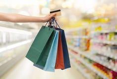 Hand mit Einkaufstaschen und Kreditkarte am Speicher Lizenzfreies Stockfoto