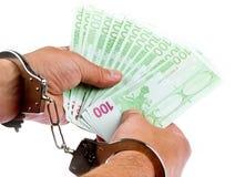 Hand mit Euro und Handschellen Stockfotografie