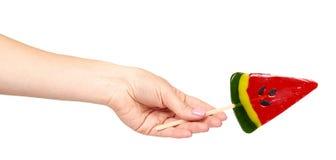 Hand mit Farblutscher, helle kühle Süßigkeit, Wassermelonenform stockfoto