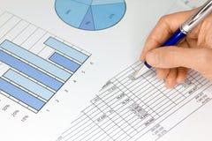 Hand mit Feder-Abbildungen und Diagrammen im Blau Stockfotos