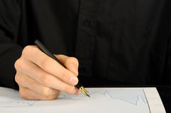 Hand mit Feder auf Diagramm lizenzfreie stockfotografie