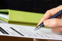 Hand mit Feder-kennzeichnendem Formular durch grünes Faltblatt lizenzfreie stockbilder
