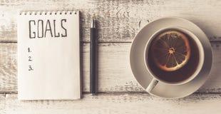 Hand mit Federschreibenszielen Notizbuch mit Zielen listen, Tasse Tee auf Holztisch auf beweggrund lizenzfreies stockfoto
