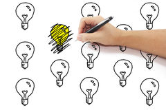 Hand mit Federzeichnung kritzelt auf gelber Glühlampeidee unter Stockfoto