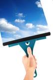 Hand mit Fensterreinigungswerkzeug und blauem Himmel Stockfotografie