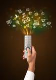 Hand mit Fernbedienungs- und Social Media-Ikonen Stockfotos