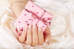 Hand mit Franzosen manikürte die Nägel, die eine Geschenkbox halten Lizenzfreie Stockbilder