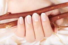 Hand mit Franzosen manikürten Nägeln Lizenzfreie Stockbilder