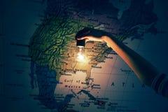 Hand mit Glühlampe auf amerikanischer Karte Stockbild