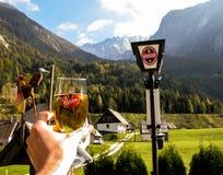 Hand mit Glas Anschlussbier. Alpine Landschaft. Stockfotografie