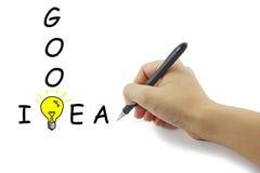 Hand mit großer gelber Glühlampe der Federzeichnung mit gutem Ideenwort lizenzfreies stockbild
