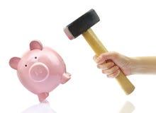 Hand mit Hammer und piggy Querneigung lizenzfreie stockfotografie
