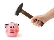 Hand mit Hammer und piggy Querneigung Lizenzfreies Stockfoto