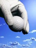 Hand mit Handschuh und Golfball stockfotos