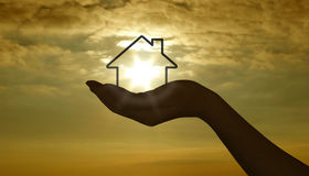 Hand mit Haus am Sonnenuntergang Lizenzfreies Stockbild