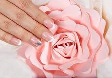 Hand mit künstlichen französischen manikürten Nägeln und rosa rosafarbener Blume lizenzfreie stockbilder