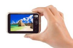 Hand mit Kamera- und Strandlandschaft (mein Foto) Lizenzfreie Stockfotos