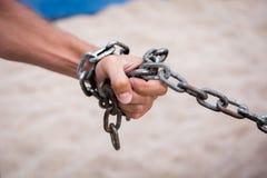 Hand mit KETTENmetall- und Sandwüste stockfotografie