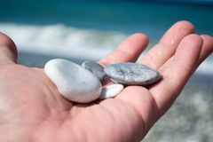 Hand mit kleinen Steinen auf dem Strand Lizenzfreie Stockfotografie