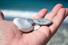 Hand mit kleinen Steinen auf dem Strand Lizenzfreie Stockfotos