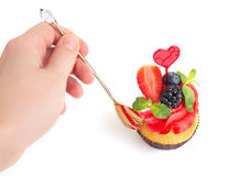 Hand mit Löffelreichweiten für kleine Kuchen Der Mann möchte kleine Kuchen essen Stockfoto