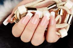 Hand mit langen künstlichen Franzosen manikürte die Nägel, die eine Halskette halten Stockbilder