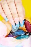 Hand mit langen künstlichen Franzosen manikürte die Nägel, die eine Halskette halten Lizenzfreies Stockbild