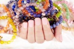 Hand mit Lech manikürte Nägel und bunte Armbänder Lizenzfreie Stockbilder