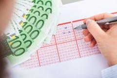 Hand mit Lottoschein und Banknoten Lizenzfreies Stockbild