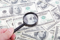 Hand mit Lupe auf einem Hintergrund von Dollarscheinen. Lizenzfreie Stockbilder