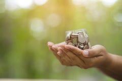 Hand mit Münzen auf bokeh Hintergrund Lizenzfreie Stockbilder