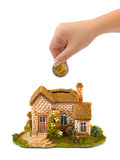 Hand mit Münzen- und Hausquerneigung stockbild