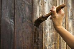 Hand mit Malerpinsel auf Holz lizenzfreie stockbilder