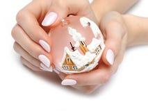 Hand mit Maniküre- und Weihnachtsbaumdekoration lizenzfreie stockfotografie
