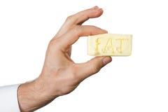 Hand mit mit einem Stück Butter Lizenzfreie Stockbilder