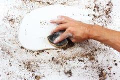 Hand mit nassem Schwamm säubert schwer schmutzige Oberfläche Lizenzfreie Stockfotos