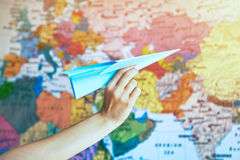 Hand mit Papierflugzeug auf Weltkarte lizenzfreies stockfoto