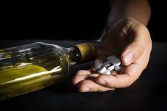 Hand mit Pillen und Whiskyflasche Stockbilder